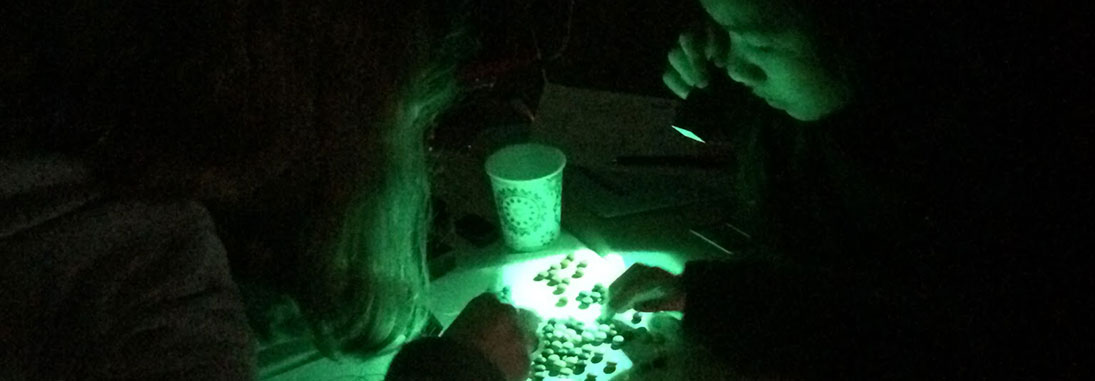two girls conducting an experiment with green light