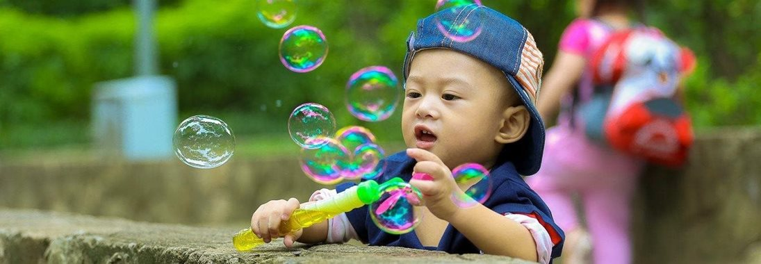 child playing with bubbles in a park